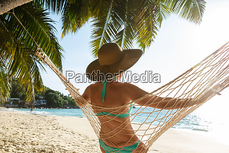 woman in bikini sitting on hammock