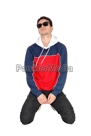 young man in sports clothing kneeling