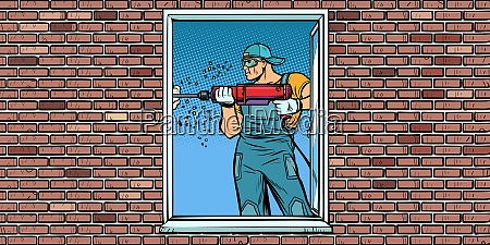 a worker installs a window drilling