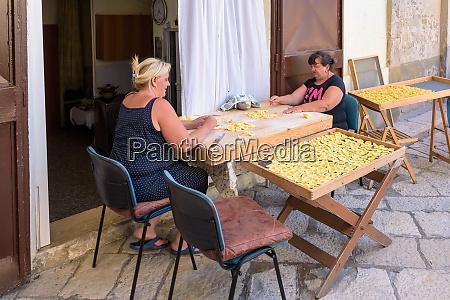 women making traditional italian pasta on