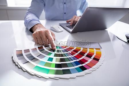 designer using laptop at desk