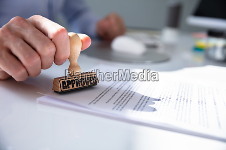 persons hand stamping with approved stamp