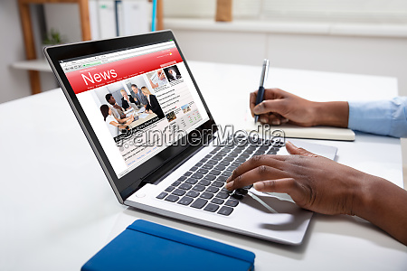 businessperson checking online news on laptop