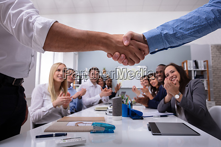team leader handshaking in front of