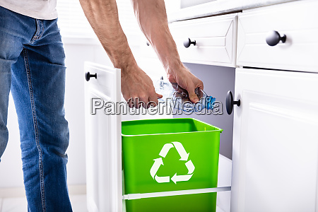 man throwing plastic bottle in recycling