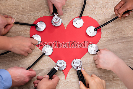 peoples hand holding stethoscope over red