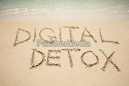 digital detox word on sand near