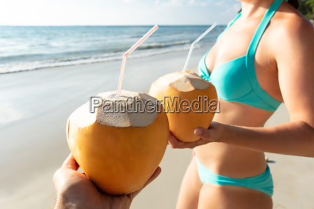 couple holding coconut with drinking straw