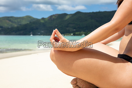 woman in bikini meditating on beach