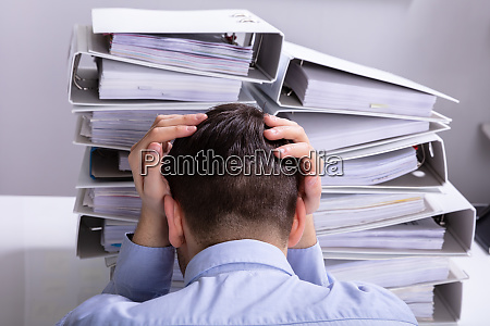 stressed businessman in front of stacked