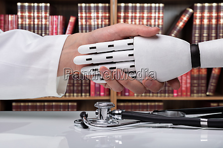 doctor and robot shaking hands over