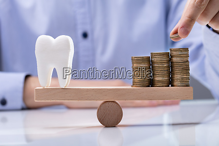 stack of coins and healthy tooth