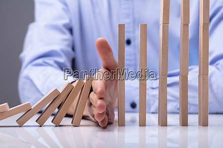businessman stopping wooden blocks from falling