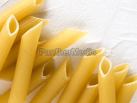 raw pasta penne on white background