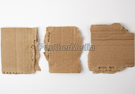 three pieces of torn brown paper