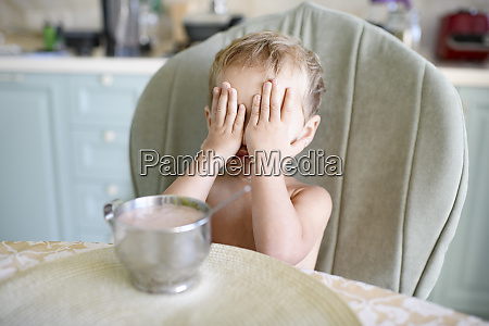 little girl at dining table covering