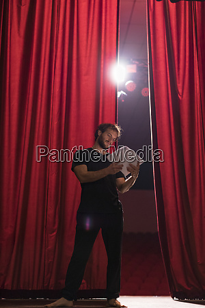 barefoot actor standing on stage of