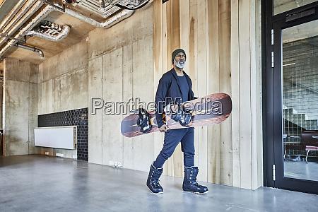 mature businessman holding snowboard in modern