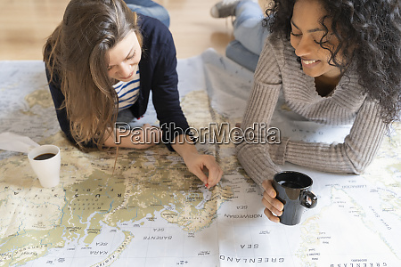 friends putting pins on a map