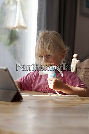 portrait of blond little girl using