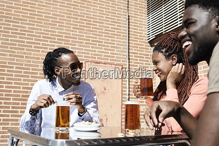 three happy friends drinking beer at