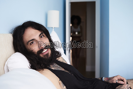 portrait of smiling tattooed man lying