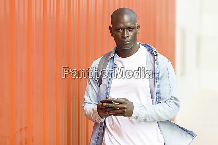 portrait of man with smartphone wearing