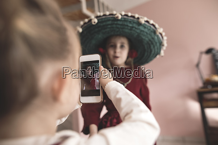 little girl taking picture of dressed