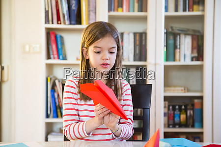 girl tinkering paper plane on table