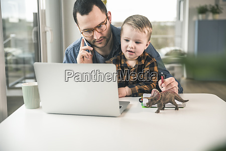 father working at table in home