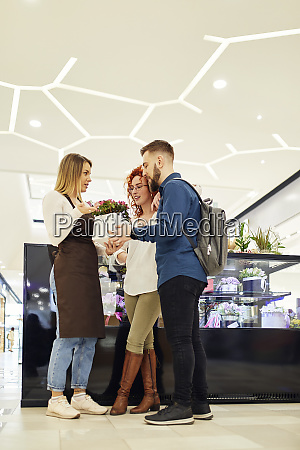 shop assistant advising couple in flower