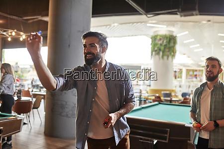 smiling man playing darts
