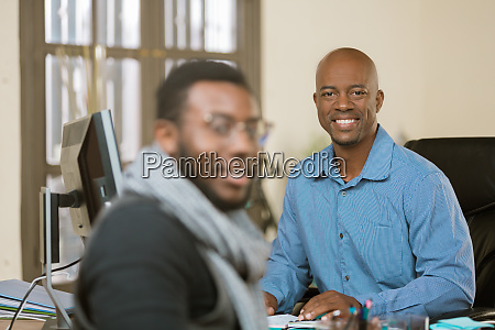 smiling business man with colleague or