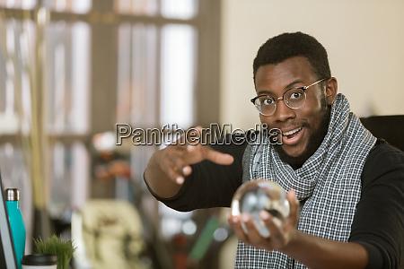 confident creative man with crystal ball