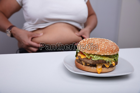 overweight woman pinching her stomach with