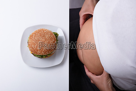 woman pinching her fatty stomach with