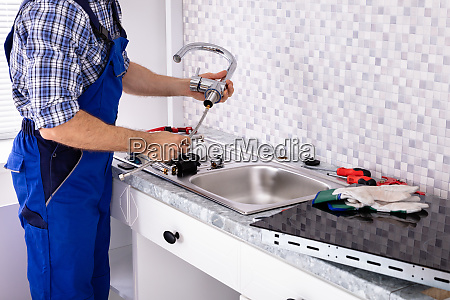 plumber assembling the kitchen sink faucet
