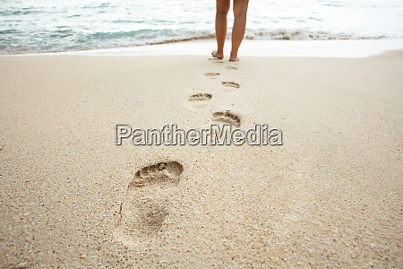 woman walking on beach leaving footprints