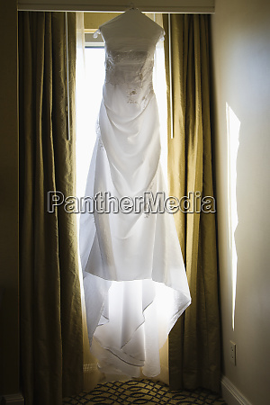 a wedding dress hanging up in