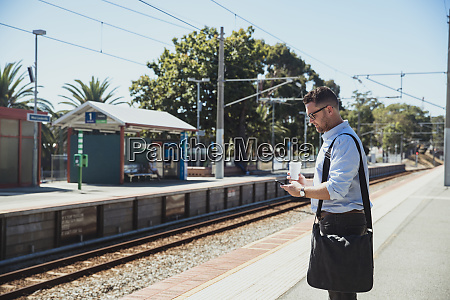 businessman using smart phone at train