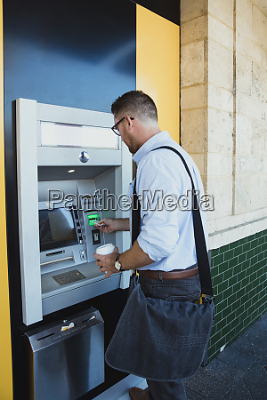 businessman using atm machine