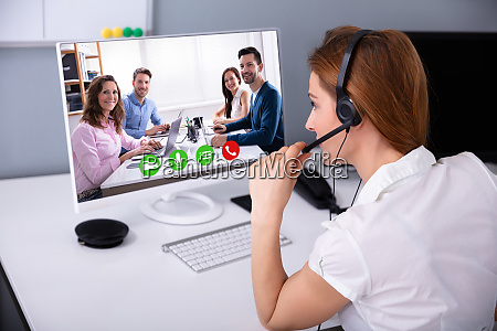 businesswoman video conferencing with her colleagues
