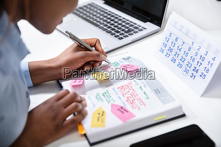 businesswomans hand checking schedule in diary