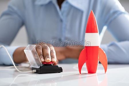 businesswomans hand launching rocket