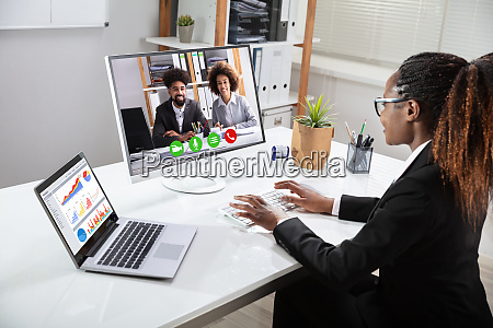 happy businesswoman videoconferencing with her colleagues