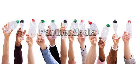 people holding crushed water bottles in