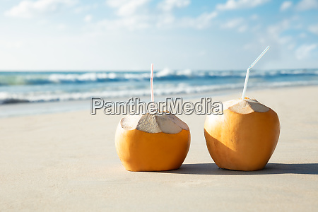 coconuts with drinking straw on sand