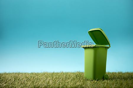green recycle bin on green grass
