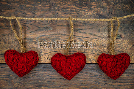 3 red cuddle hearts on antique