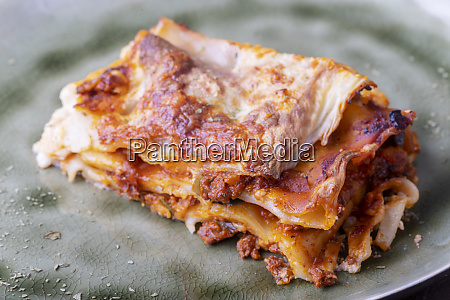cooked lasagna on a green plate